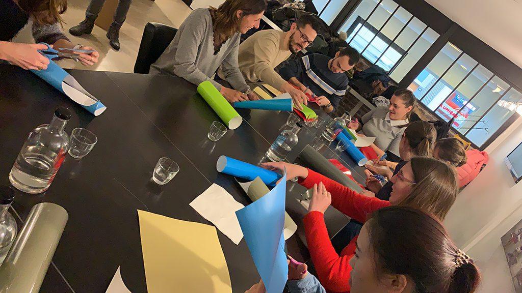 des collaborateurs assis autour d'une table de réunion découpent des formes dans des adhésifs de couleurs