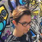 une artiste d'art contextuel qui porte des lunette en train de créer une œuvre d'art en direct dans son tableau coloré