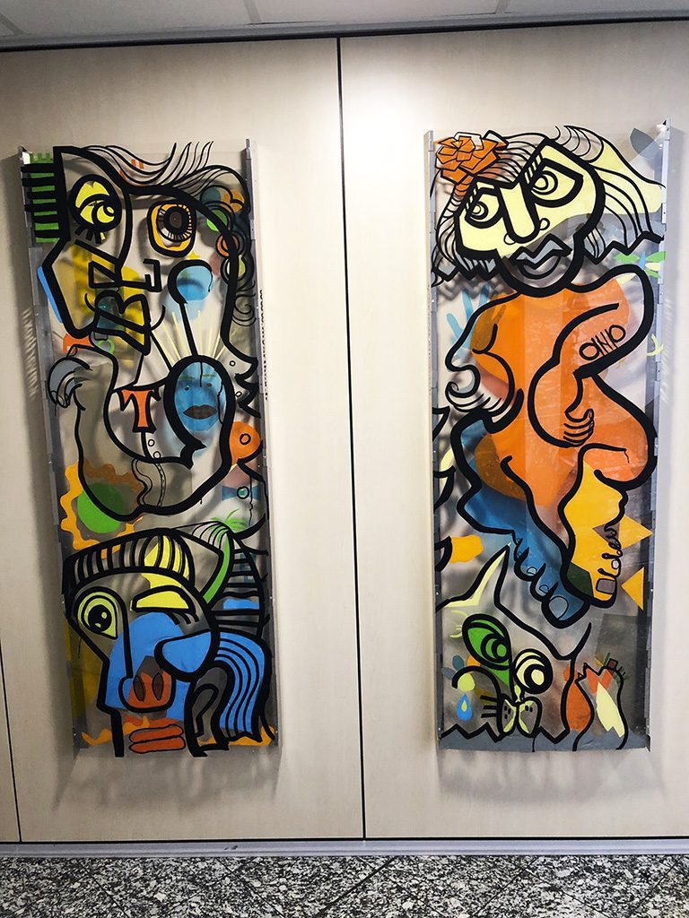 deux tableaux colorés accrochés au mur d'une entreprise