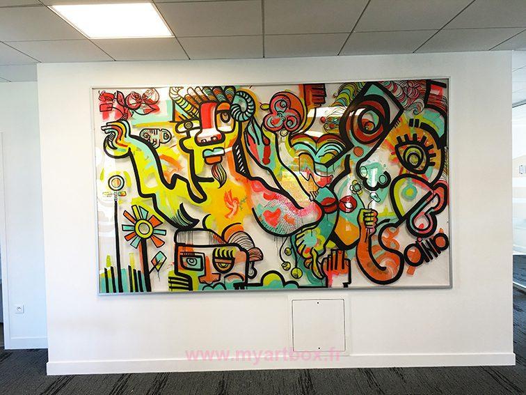 une fresque collective sur plexiglass encadrée et exposée dans un espace commun d'une entreprise
