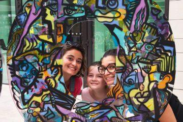 trois générations de femmes posent au milieu d'une œuvre d'art en forme de O