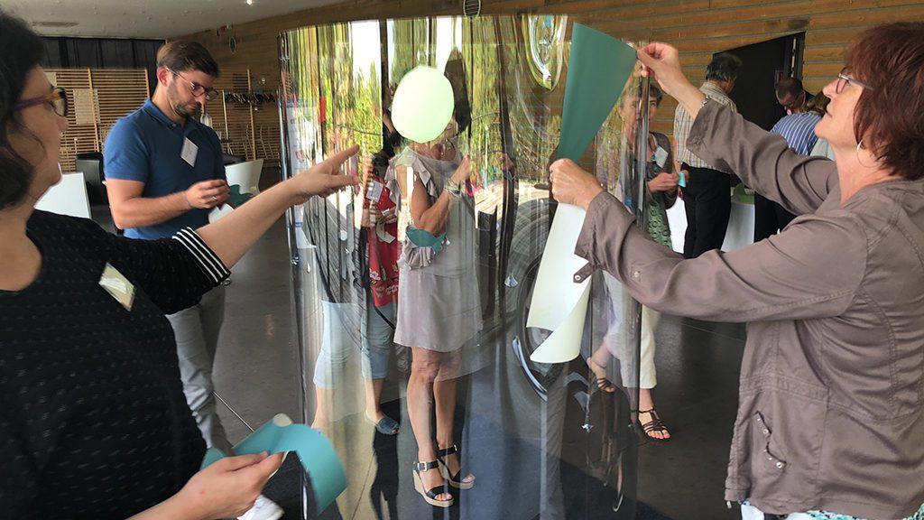 des personnes collent des formes originales sur un tube transparent lors d'un team building