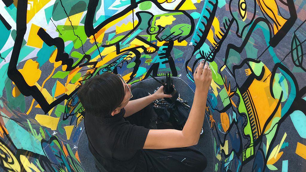 Team Building Artistique original : une femme peint à l'intérieur d'un cylindre géant