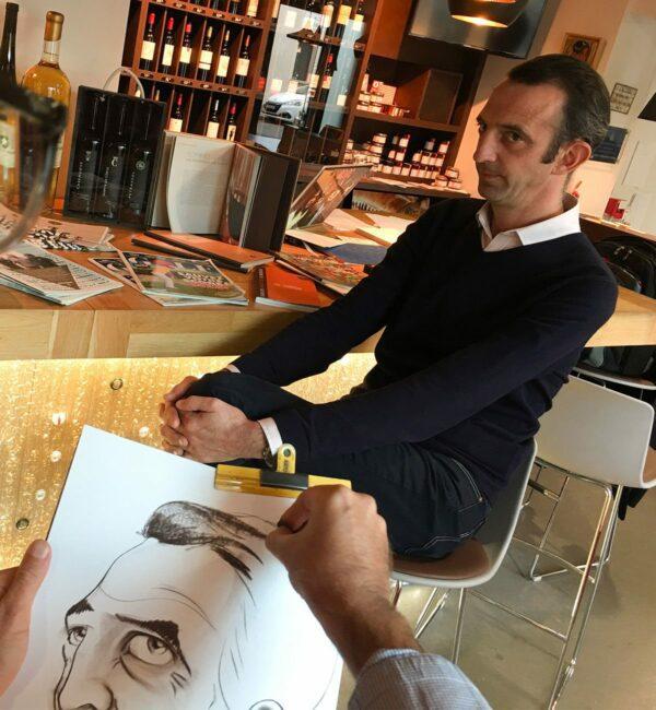 un modèle homme assis pose en face d'un caricaturiste qui le dessine sur feuille de papier format A3 en noir et blanc