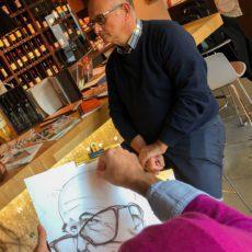 un artiste caricaturiste réalise le dessin noir et blanc format A3 en direct en face de son modèle à Lyon