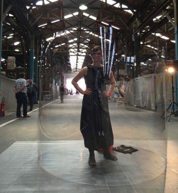 L'artiste aNa vêtue de noir positionnée dans son tube fresque plexi art à Lyon avant l'arrivée des participants à un team building tube inaugural