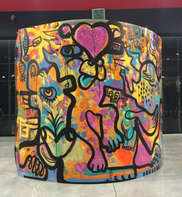image d'une fresque roulée en cylindre de l'artiste aNa présentant des personnages au trait noir dessinés sur peinture multicolore sur plexi au milieu d'un hall de palais des congrès de Bourg-en-bresse Ainter expo en fin de journée d'un team building tube pour 800 personnes