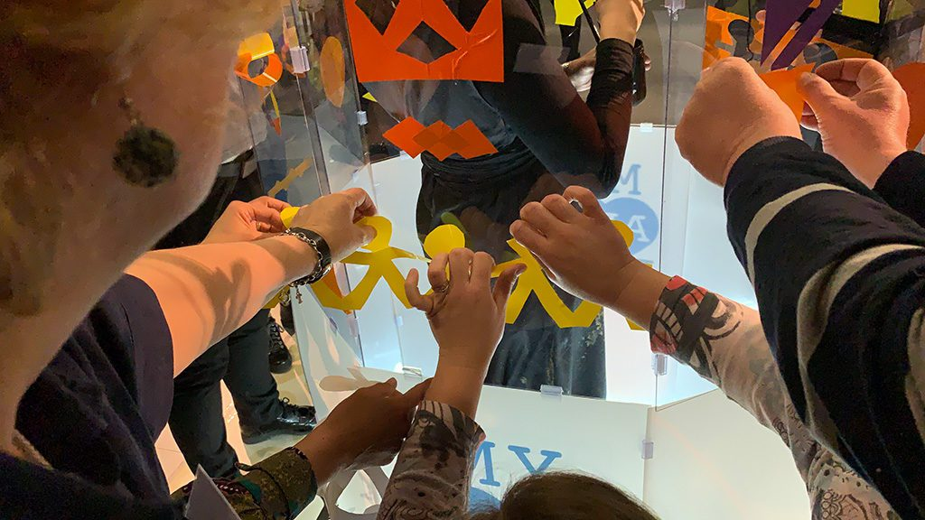 brainstorming de collaborateurs d'entreprise en atelier team building fresque plexi qui découpent des forment colorées collées sur le tube transparent de l'artiste aNa