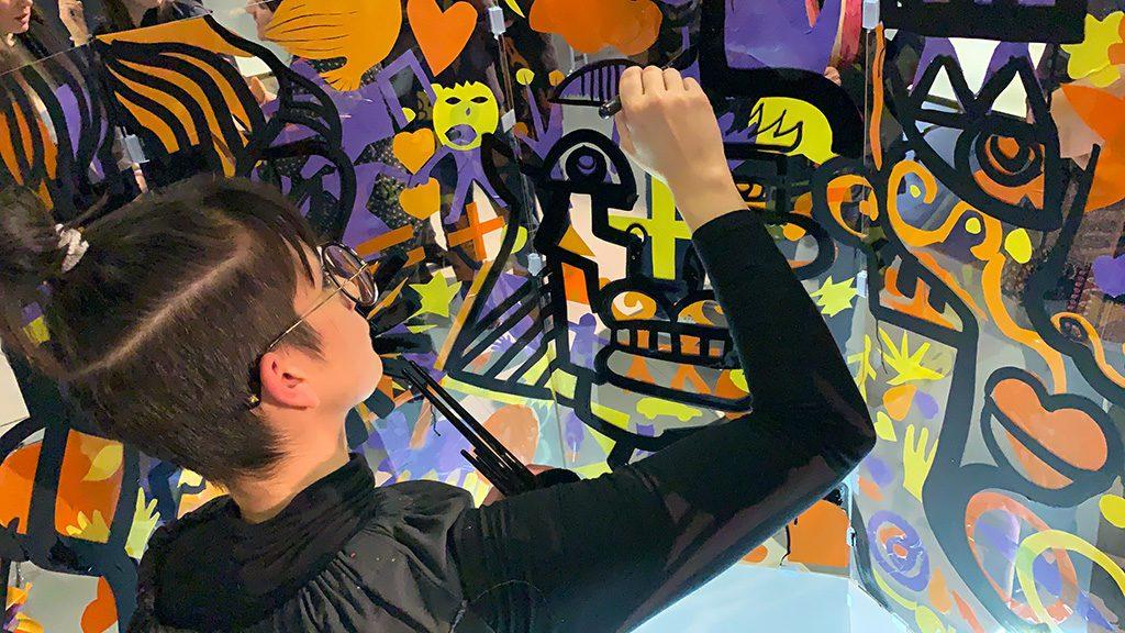 L'artiste aNa en train de peindre une fresque cylindre transparent en atelier team building