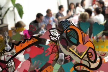 détail d'une œuvre aNa artiste plexi art au premier plan devant une tablée de banquet familial