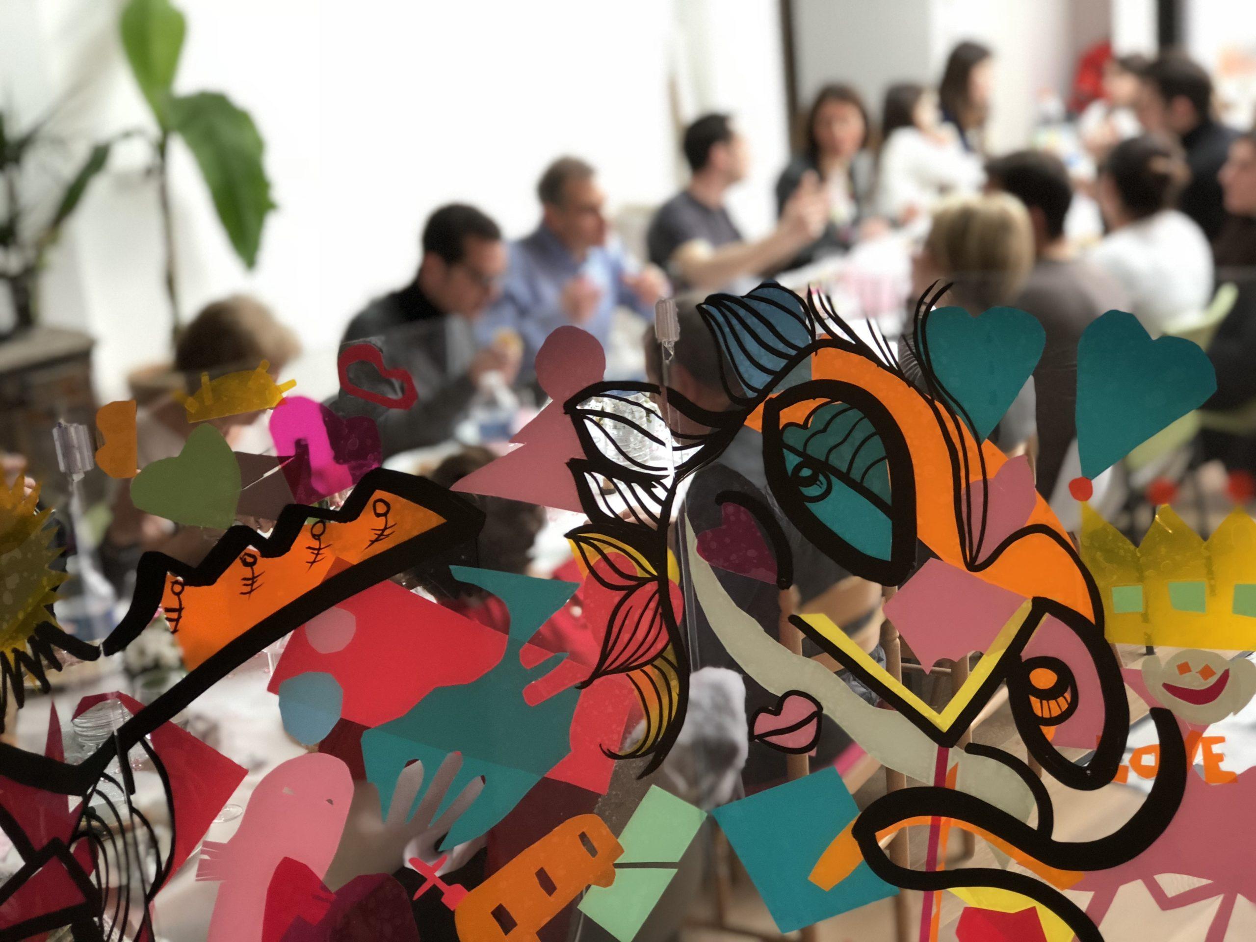 Animation Brainstorming : détail d'une œuvre aNa artiste plexi art au premier plan devant une tablée de banquet familial