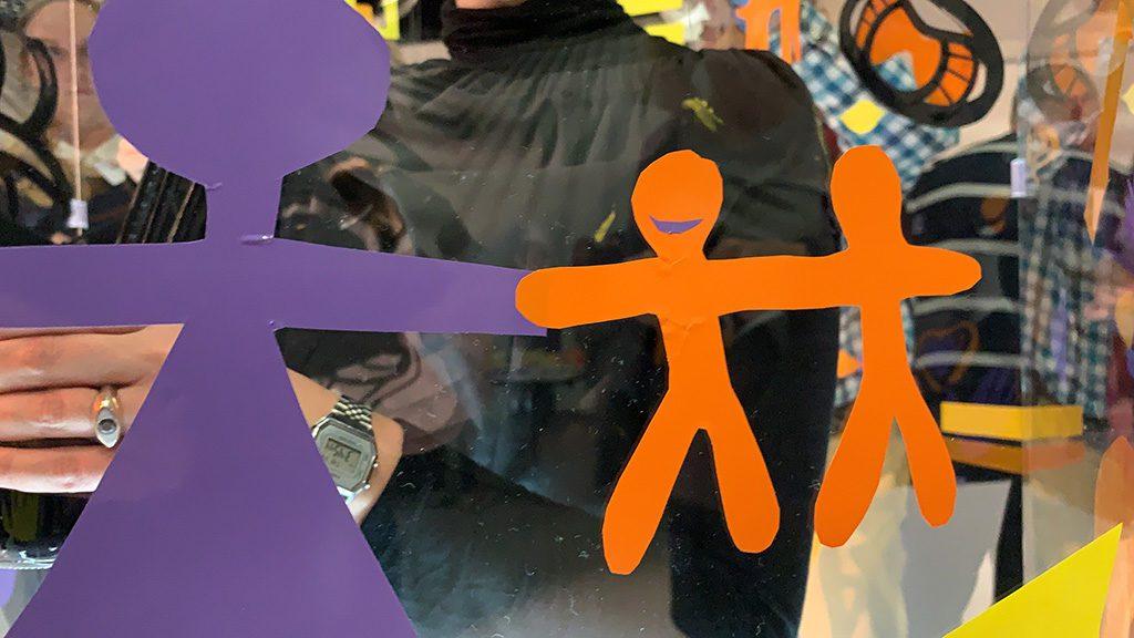 découpage de formes de personnages en couleurs collées sur un tube géant transparent en animation créative pour le salon préventica