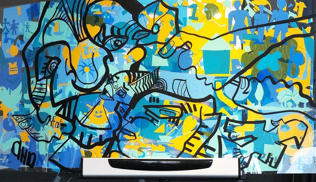 fresque graffiti plexi my art box faite avec des adhésifs colorés jaunes bleus et verts collés sur une plaque de plexiglass transparent