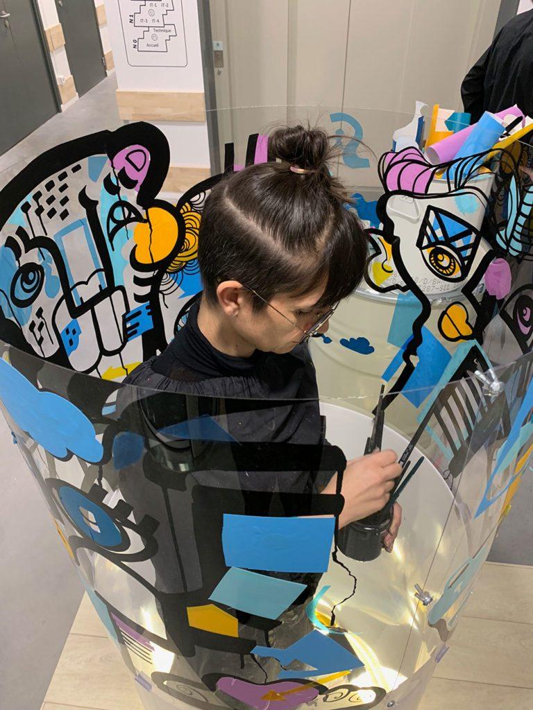 une artiste dans un tube transparent en live painting lors du salon préventica