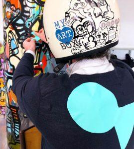 un homme qui porte un casque blanc décoré par l'artiste aNa pour myartbox en pull bleu avec un poisson d'avril géant vert collé dans le dos