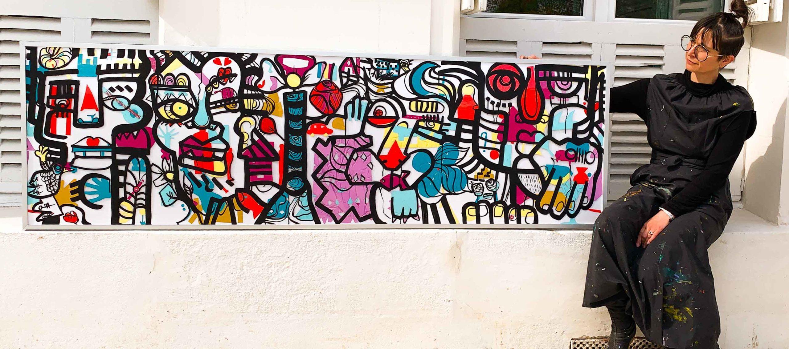 10 Idées Cadeaux Cagnotte Anniversaire - aNa artiste devant une œuvre collective encadrée peinte lors d'un team Building Tours