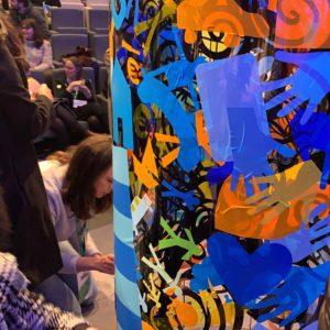 des personnes collent des adhésifs de couleurs sur un plexi transparent lors d'une animation fresque