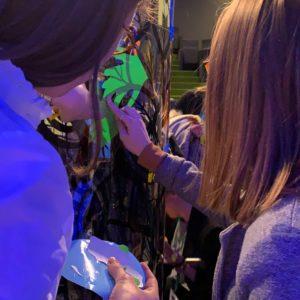 Des jeunes filles participent à un exercice de cohésion animation fresque en coulant une main verte découpées dans du vinyle de couleur sur un Tube plexi Totem Box XL my art box de l'artiste aNa