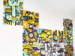Des plaques de plexi transparent sont décorées de multiples motifs et couleurs et associées entre elles avec des clips plastiques lors d'une animation TP pour exercice de cohésion d'équipe, team building créatif et brainstorming original