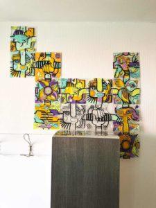 Une fresque évolutive happiness management composée de plaques de plexi décorées de vinyle de couleurs et assemblées librement autour d'un meuble dans une petite entreprise aux murs blancs