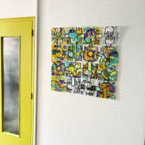 Tableau décoratif composé de plaques de plexiglass dessinées par l'artiste aNa et associées pour former une composition originale sur un mur blanc à coté d'une porte de séparation verte