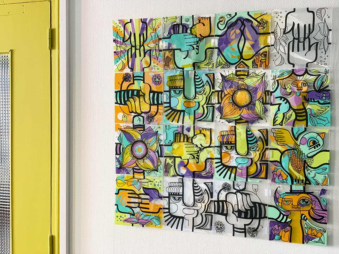 Une Animation Télétravail : tableau coloré composé de 16 pièces de plexi assemblé lors d'une idée animation tététravail possible grâce au kit puzzle à distance My Art Box