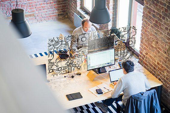 Paroi de protection plexiglass - vue de dessus d'un bureau commun occupé par deux hommes dans un loft en briques rouges et séparés par une décoration brise vue puzzle my art box